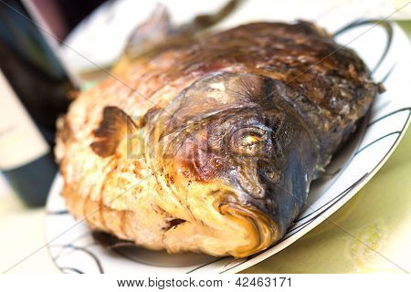 Baked carp in a plate with wine in background poster
