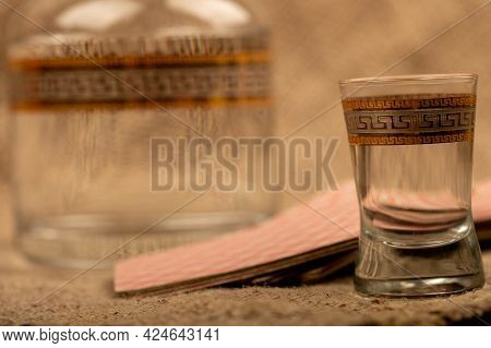 A Glass Decanter With Vodka And A Glass Of Vodka On The Background Of A Homespun Fabric With A Rough