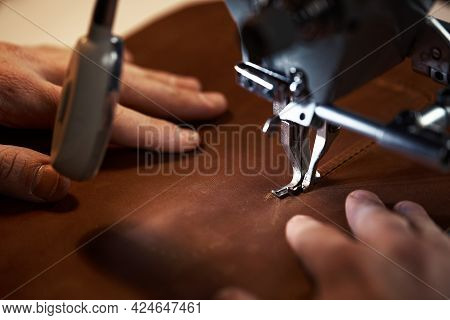 Leatherworker Workflow. A Tanner Or Skinner Sews Leather On A Special Sewing Machine. A Worker Sews