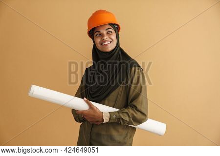 Black muslim woman in helmet smiling while posing with drawing isolated over beige background