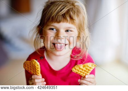 Portrait Of Happy Little Preschool Girl Holding Fresh Baked Heart Waffle. Smiling Hungry Toddler Chi