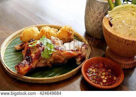 Traditional Thai Grilled Chicken With Fried Sticky Rice Mix Egg On Threshing Basket With Banana Leaf