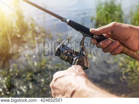 Fisherman Hands Closeup Holding Spinning Reel Rod Or Spoon Bait. Summer Fishing On Sunny Weather.