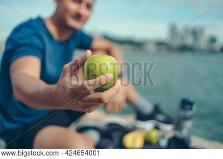 Healthy Man Hold Apple Fruit And Sitting On The Stone Near The Beach. Water Bottle, Banana, Earphone