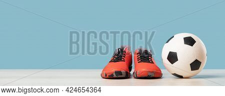 Soccer Ball With Orange Cleats Against Blue Background, Front View With Copy Space, Football Or Spor