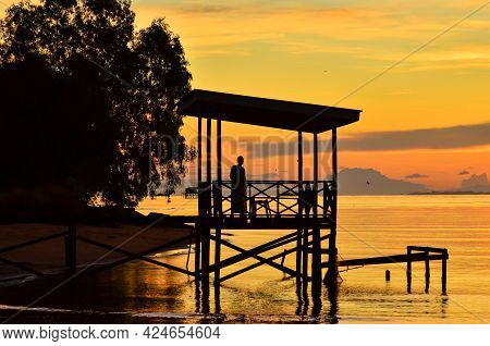 Golden Sunrise With Silhouette Of Wooden Jetty And Tropical Tree At Lubuk Temiang Beach,labuan Ft,ma