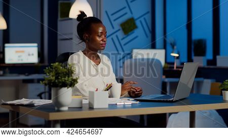 African Manager Speaking Online With Remotely Coworkers Late At Night Using Laptop Sitting In Busine