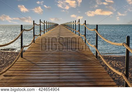 Wooden Pier Extending Into The Sea For Tourist At Sunrise.