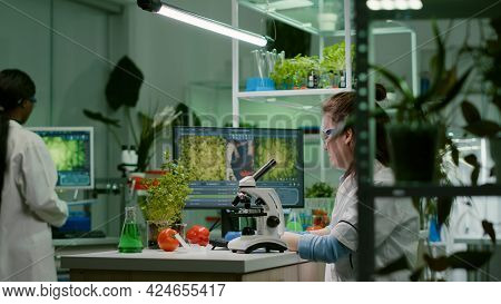 Biochemistry Doctor Examining Chemical Test Using Microscope For Genetic Researcher. Biologist Speci
