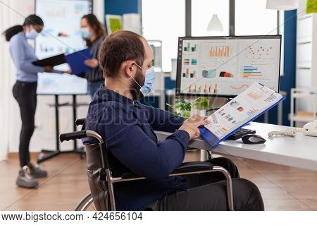 Handicapped Entrepreneur With Protective Face Mask Working In New Normal Business Financial Company