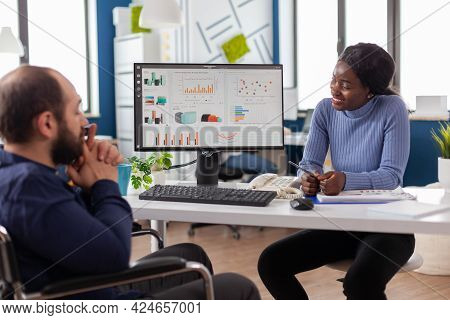 Black Manager Woman Working With Financial Documents Checking Graphs Talking With Paralysed Team Lea