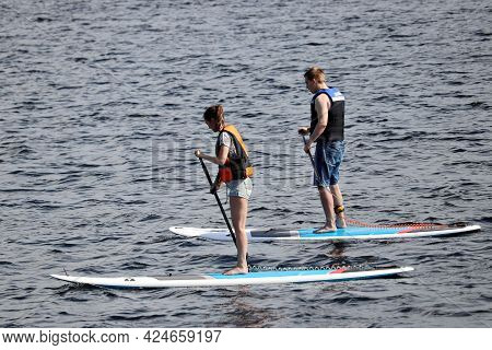 Moscow, Russia - June 2021: Sup Surfing, Couple With Paddles Sailing On A Boards In Moscow River. St