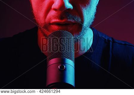 Cropped View Of Man Recording Podcast. Modern Condencer Microphone And Human Mouth In Neon Lights.