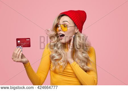 Excited Young Hipster Female In Knitted Hat And Sunglasses Looking At Credit Card With Astonishment