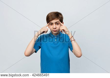 Serious Boy 12-14 Years Old Wearing Casual Blue T Shirt Pointing To Head With Two Fingers, Great Ide