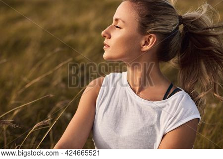 Relaxed Young Female With Eyes Closed Resting In Grassy Field And Enjoying Fresh Wind While Spending