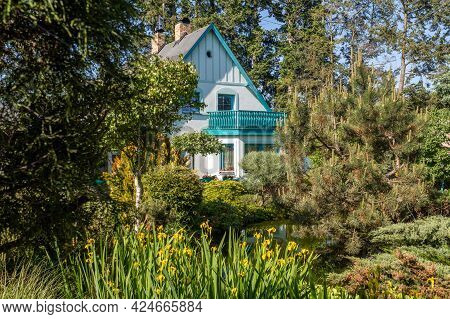 Beautiful Country House Situated In Garden, With Conifers, Trees And Flower. Summer Beautiful Garden