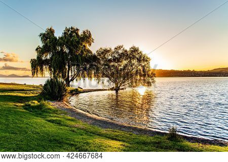 Magnificent sunset. Taupo is the largest lake in New Zealand, North Island.  The most popular holiday destinations for tourists. Quiet evening on the lake.