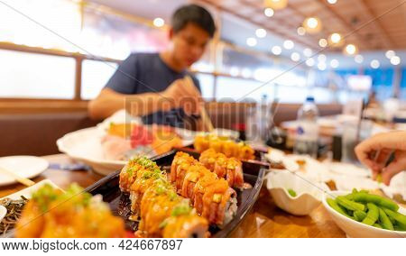 Selective Focus On Japanese Food In A Japanese Restaurant. Salmon Sushi On A Plate With Blurred Man