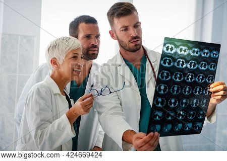 Radiologist Doctor Consulting With Colleagues An X-ray Scan In Hospital.