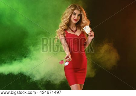 Blonde Girl In Red Dress. Smiling, Holding Or Throwing Something, Showing Two Aces, Posing On Colorf