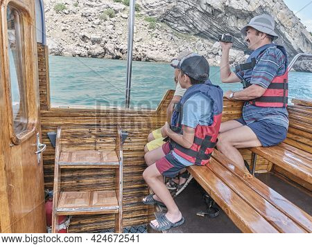 Asian Older Man And Two Boys, His Grandsons, In Life Jackets Trip On Pleasure Boat On The Sea.