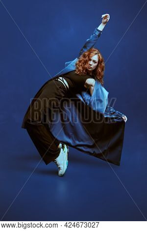 Professional modern style dancer dancing at studio on a dark blue background