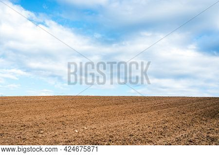 Plowed Brown Field And White Clouds On Blue Sky.cloudy Sky Over Brown Field.nice Spring Summer Day.
