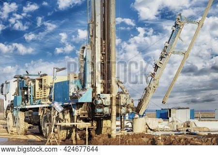 Drilling Rig In A Field Under A Blue Cloudy Sky. Drilling Deep Wells. Geological Exploration. Minera