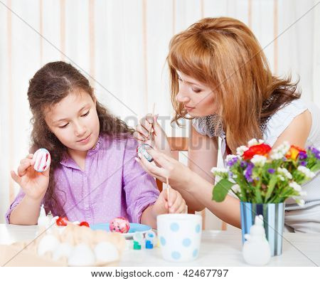 Happy mother and her little daughter painting on Easter eggs poster