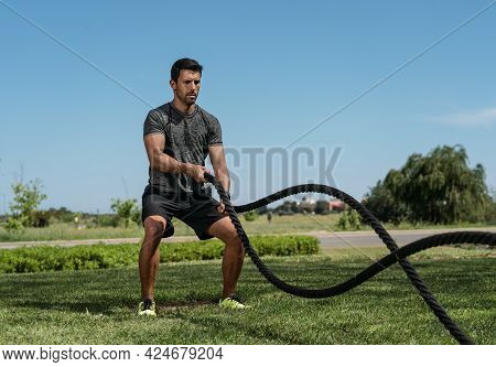 Male Athlete On The Outdoor In The Park, Exercises For Endurance, Using A Thick Rope, For Cross Fitn