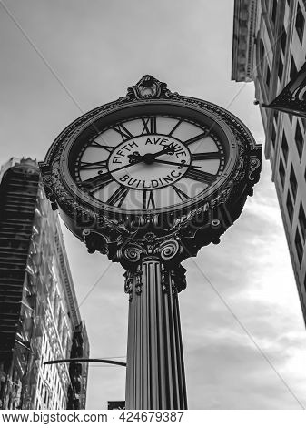 Grayscale Photo Of The Fifth Avenue Building Street Clock With Flatiron Building In Blurry Backgroun