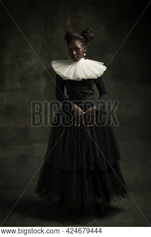 Medieval African Young Woman In Black Vintage Dress With Big White Collar Posing Isolated On Dark Gr