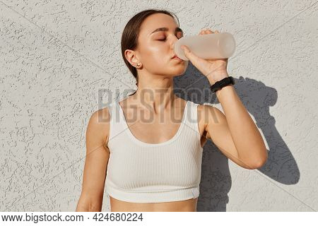 Portrait Of Tired Fitness Girl Feeling Thirsty After Sports Exercises Drinking Water From Bottle, Ke