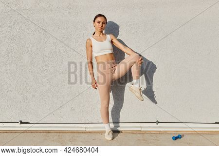 Attractive Fitness Model Girl Posing Near Gray Wall Wearing White Sport Top And Beige Leggins, Stand