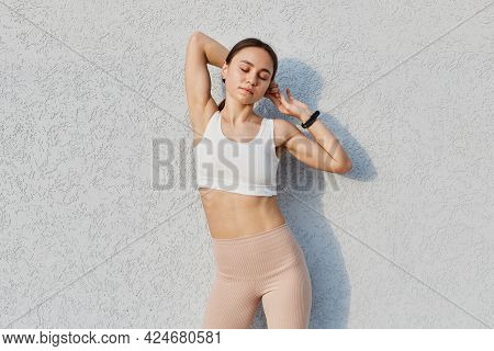 Outdoor Shot Of Calm Relaxed Beautiful Female With Dark Hair, Woman Raising Arms, Keeping Eyes Close