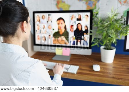 Woman Communicating With Group Of Business People Via Video Conferencing