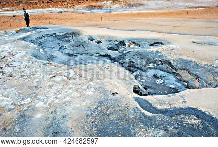 Young Woman In Overalls Traveling In Hverir Geothermal Area In North Of Iceland, Boiling Volcano Mud