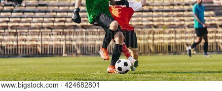 Two Football Players Running In Match. Soccer Tournament Game. Sideline Football Referee In The Back
