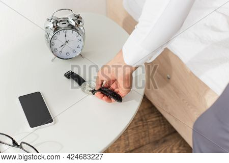 Cropped View Of Businessman Taking Wristwatch From Bedside Table Near Smartphone And Eyeglasses
