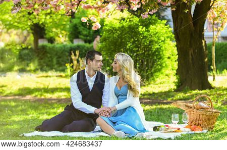 Romantic Date. Couple Relaxing At Green Meadow With Picnic Basket. Celebrate Love. Vintage Style. Co