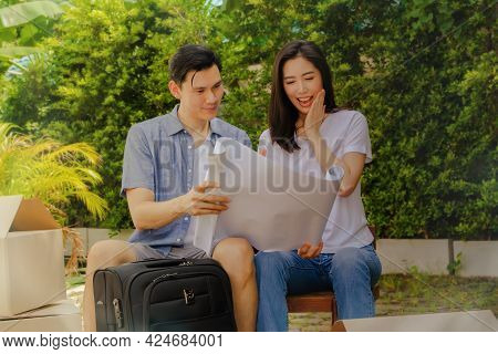 The Couple Was Delighted With Their New Home Plan, Excited Together As They Sat In Wooden Chairs Pre
