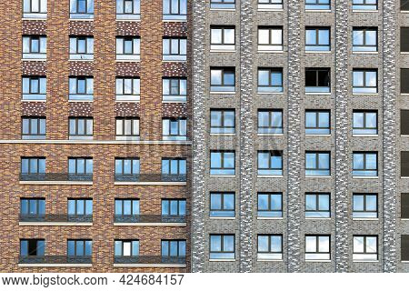 The Facade Of A Residential High-rise Building In Brown And Gray Tones. Rows Of Windows. Urban Resid
