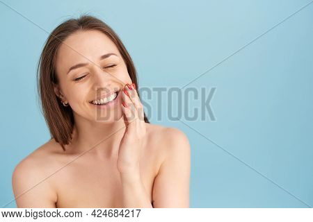 Smiling Woman Touching Her Face Against A Blue Background. Natural Beauty Concept, Happy Woman