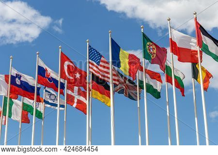 Flags Of Various States Waving In The Wind Against The Background Of The Cloudy Sky. Flags Of Variou