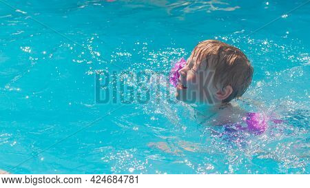 A Preschool Boy Learns To Swim In Armbands In The Pool In The Summer.
