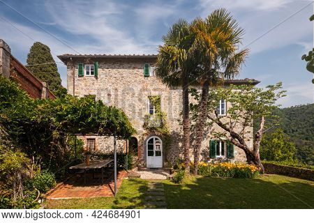 Beautiful Italian farmhouse in Tuscany surrounded by nature with a large garden. The season is summer and the sun is shining.