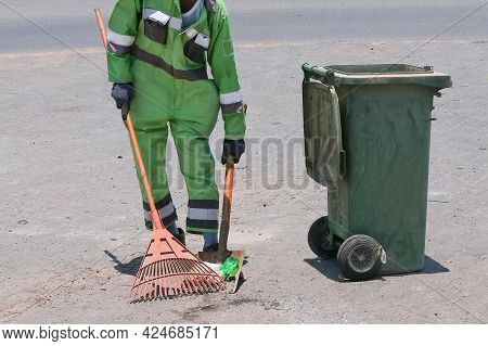 Street Cleaning, Male Municipal Worker In Fluorescent Uniform Collecting Street Rubbish To Dumpster.