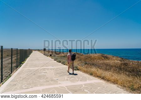 Man Tourist With Backpack Walk Along Walking Path At Rocky Coast Of Mediterranean Sea In City Paphos