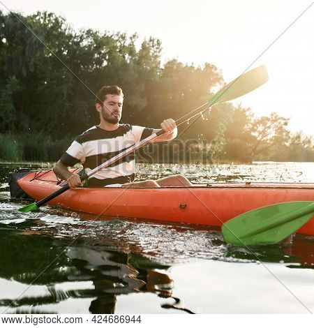 Focused Young Man Kayaking Together With His Friend In A Lake On A Late Summer Afternoon. Kayaking,